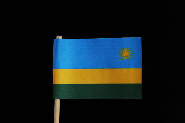 A official flag of Rwanda on toothpick on black background. A horizontal tricolour of blue, yellow and green with yellow sun in blue field A official flag of Rwanda on toothpick on black background. A horizontal tricolour of blue, yellow and green with yellow sun in blue field. genocide stock pictures, royalty-free photos & images