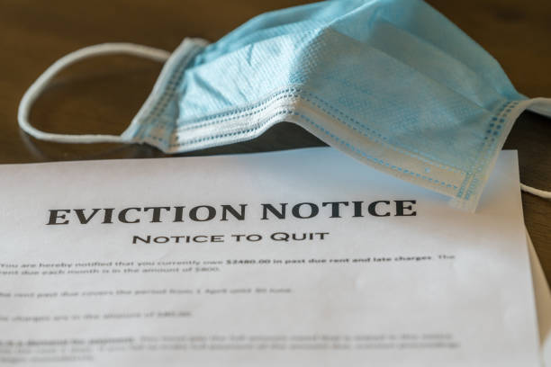 Official legal eviction order or notice to renter or tenant of home with face mask stock photo