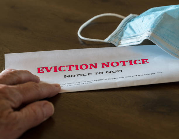 Official legal eviction order or notice to renter or tenant of home with face mask Defaulting renter with facemask receives letter giving notice of eviction from home on wooden table information sign stock pictures, royalty-free photos & images
