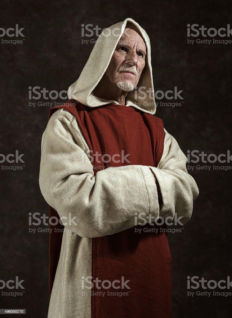 Official portrait of monastic. Studio shot against dark wall. stock photo