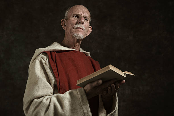 Official portrait of monk holding book. Against dark wall. Official portrait of monk holding book. Studio shot against dark wall. friar stock pictures, royalty-free photos & images