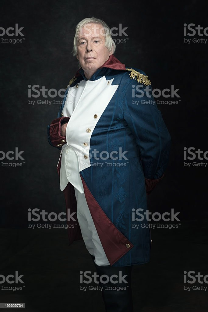 Official portrait of senior man dressed in historical emperor costume. stock photo