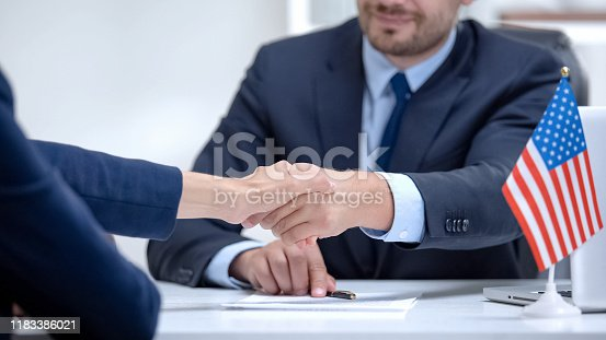 istock US official signing contract for international cooperation, shaking partner hand 1183386021
