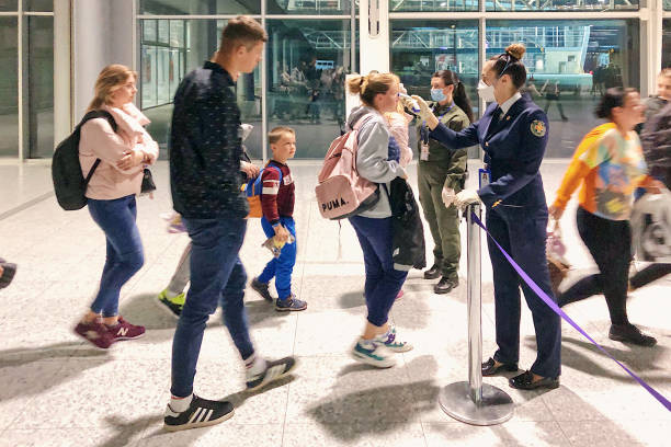 Officials and medics wearing medical face masks check temperature of arrived passengers using contactless thermometers at the local airport to prevent the spread of coronavirus COVID-19 or 2019-nCoV stock photo
