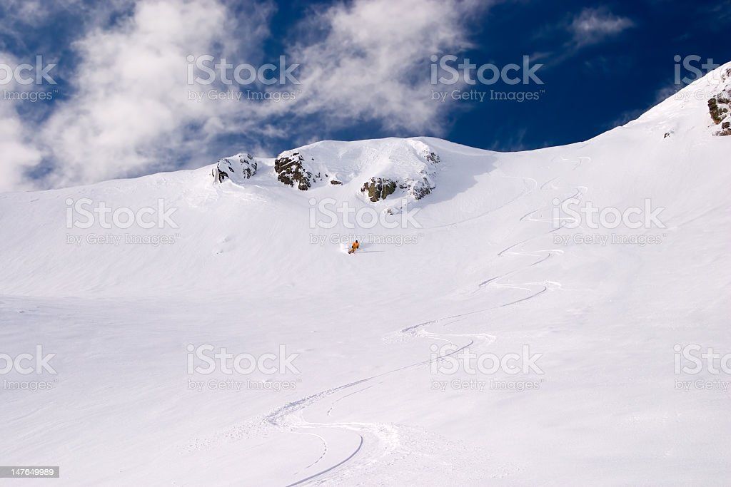Off-piste skier following the first tracks on a slope stock photo