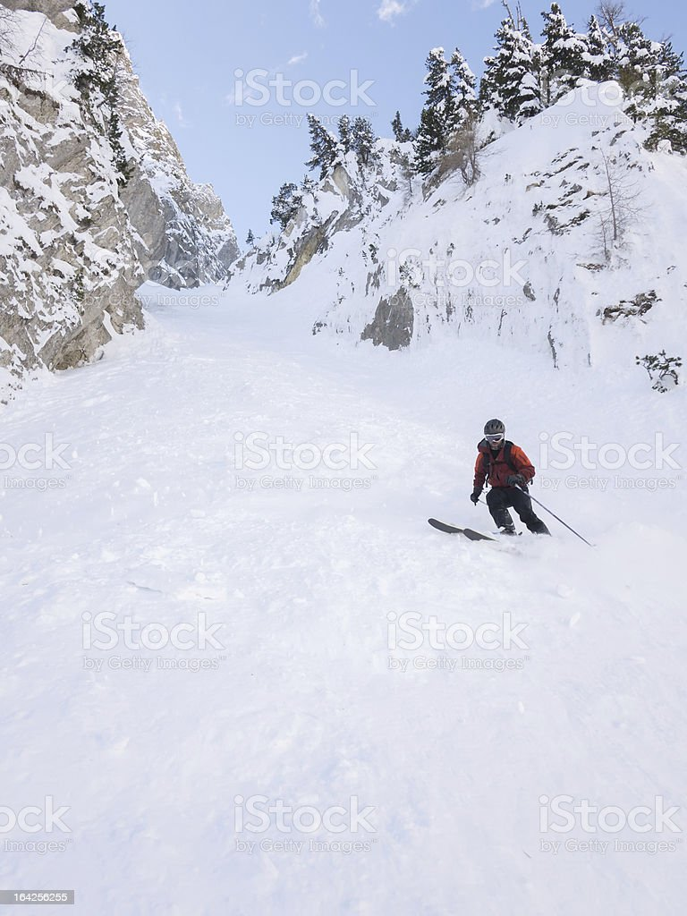 Off-piste skier in a steep chute royalty-free stock photo