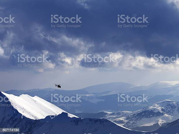 Photo of Off-piste slope for heliskiing and helicopter in evening