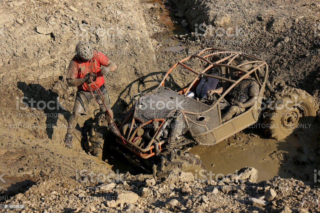 Offroad 4wd race - 4wd vehicle preparing to scale uphill from mud with car winch. Copilot is pulling the winch stock photo