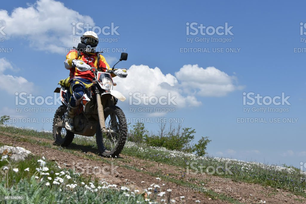 Motorcyclists with helmet and sportswear riding his bike on a dirt...