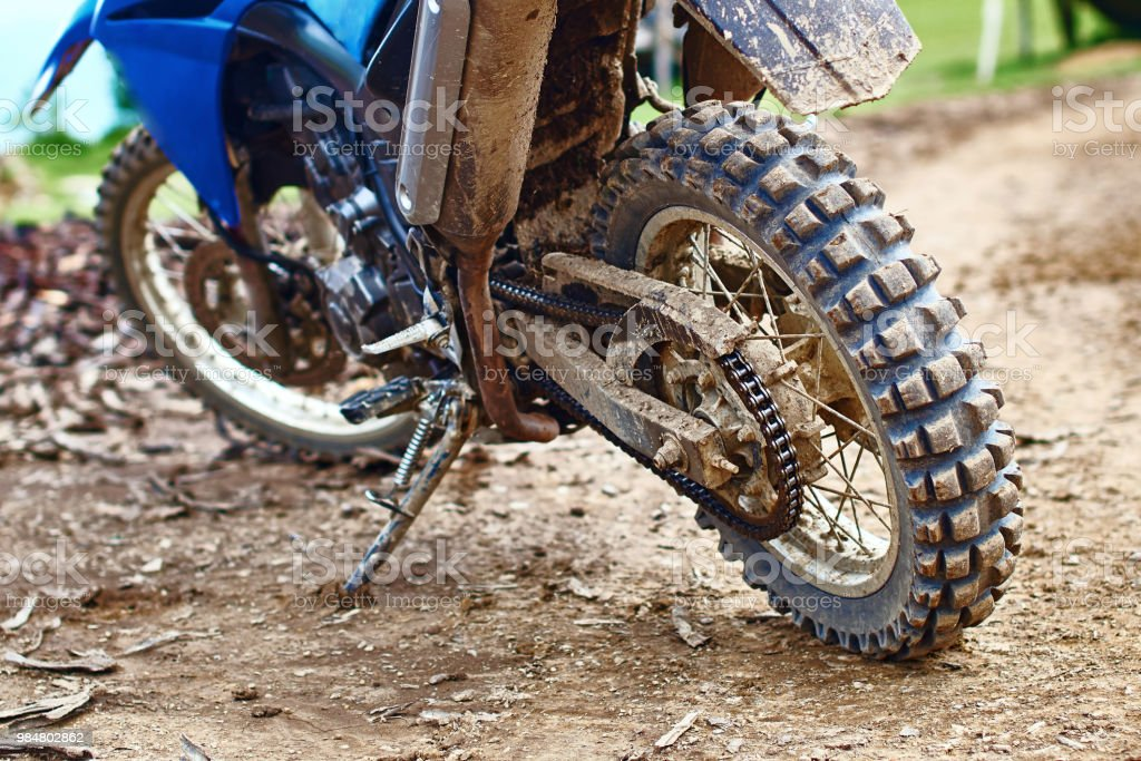 Offroad mountain motorcycle or bike taking part in motocros competition parked on dirty terrain road stock photo