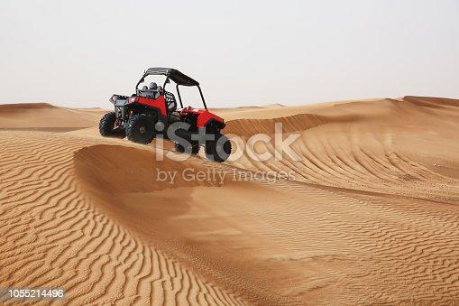 Off-road SUV vehicle speeding through sand dunes in the Arabian desert