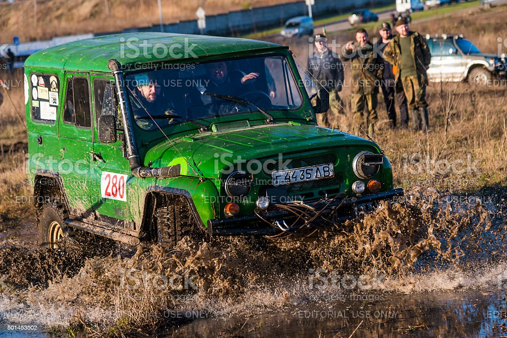 Off-road vehicle brand UAZ overcomes the track on a polygon stock photo