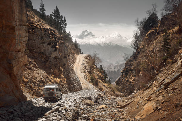 Off-road vehicle goes an extreme mountain path during an expedition to Himalayas Off-road travel on extreme mountain road in Upper Mustang, Nepal. Nice view of the Himalaya Mountains steep stock pictures, royalty-free photos & images