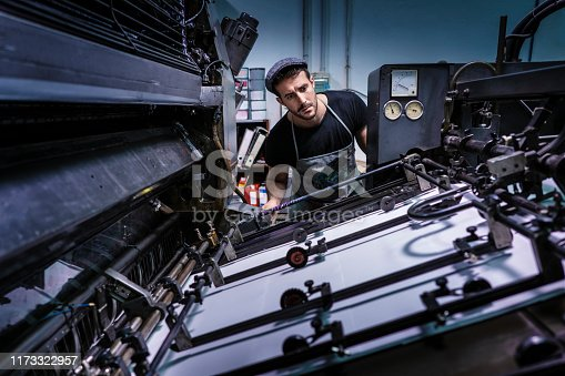 Offset printer man with 2 colors printer working in printing industry