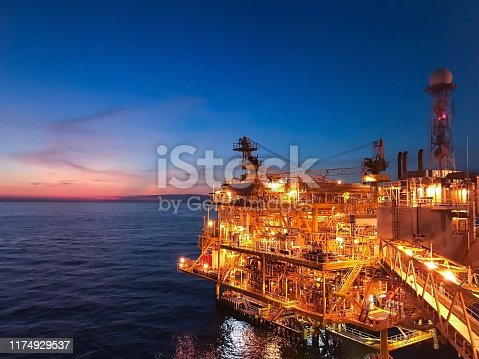 Offshore construction platform for exploration and production oil and gas with bridge in evening time for power energy of the world concept