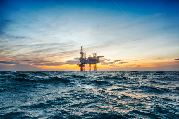 offshore drilling rig at sunset - benzina foto e immagini stock