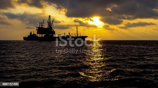 Drilling rig with FPSO facilty in sunset.