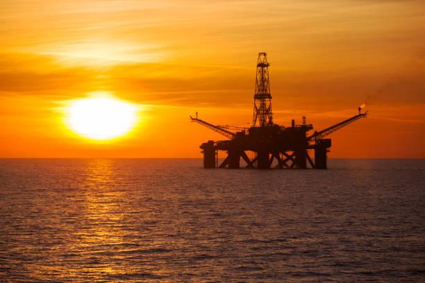 Offshore-Anlage mitten im Meer bei Sonnenuntergang – Foto