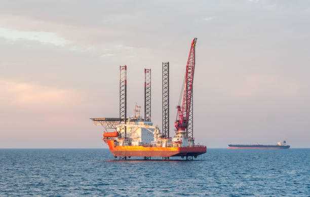 Offshore jack-up barge and an oil tanker Flat-bottomed offshore jack-up barge and an oil tanker on the horizon at some Arabian oilfield. rigging stock pictures, royalty-free photos & images