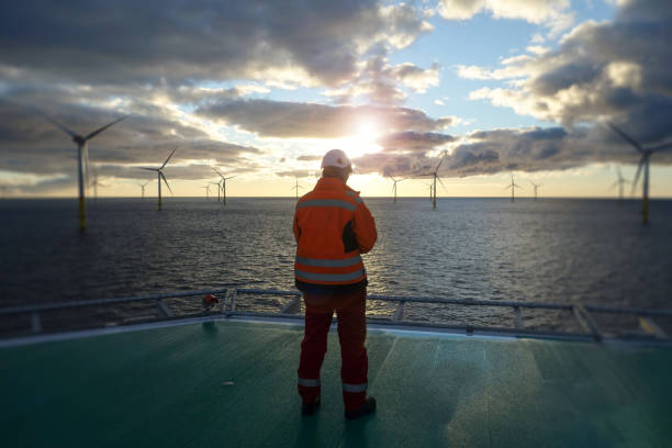 Offshore manual worker standing on helipad with wind-turbines behind him in sunset Wind-turbine, offshore, worker, climbing, sun, big, deck, vessel windmill stock pictures, royalty-free photos & images
