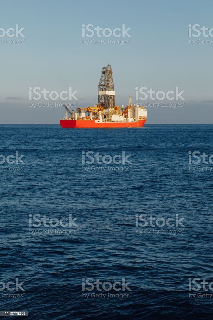offshore oil and gas red drillship, blue ocean background