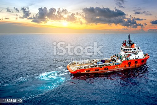 Supply boat offshore oil rig on loading operation with cloudy sky and blue ocean background.