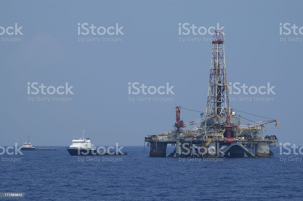 Jack up oil drilling rig with work vessel. Offshore oil rig