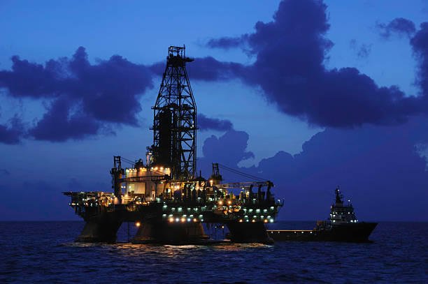 Offshore oil rig at night with supply boat