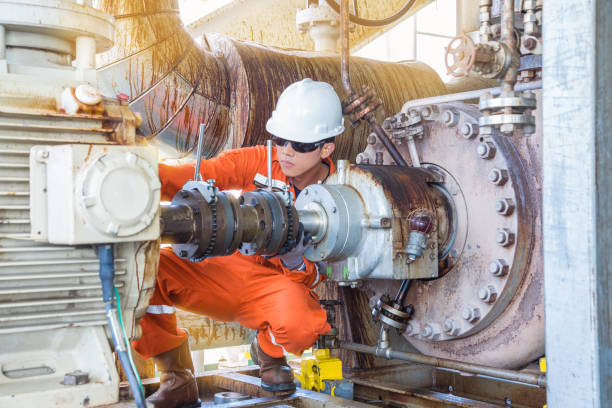 Offshore Oil Rig worker, Mechanical technician inspecting oil centrifugal pump alignment to prevent vibration which damage bearing and mechanical seal systems. Offshore Oil Rig worker, Mechanical technician inspecting oil centrifugal pump alignment to prevent vibration which damage bearing and mechanical seal systems. centrifuge stock pictures, royalty-free photos & images