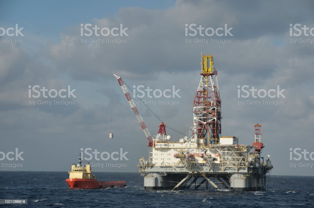 A floating offshore drilling platform using a crane to take on...