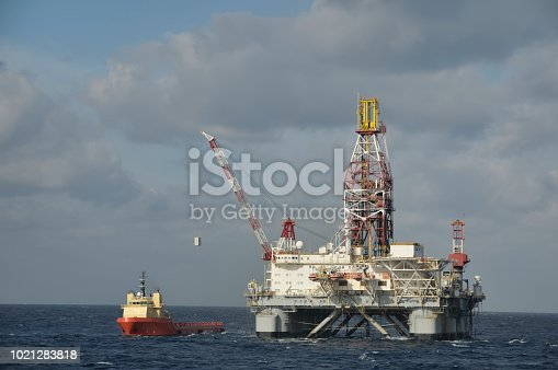 A floating offshore drilling platform using a crane to take on supplies from a support vessel.