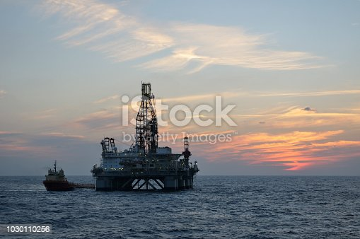 An oil rig supply vessel sits alongside a semisubmersible floating drilling platform with glow from the sun low in the sky.
