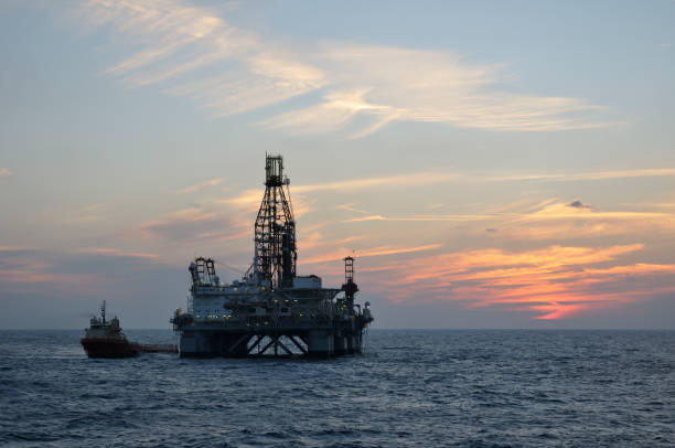Offshore semisubmersible oil rig with a supply vessel at twilight