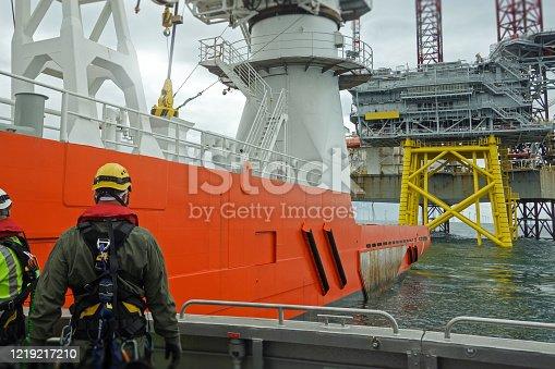 Technician standing on passenger ship deck and preparing for transfer on big transfer vessel. Offshore platform behind.