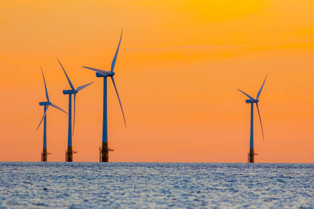 offshore wind farm energy turbines at dawn. surreal but natural sunrise at sea. - wind stock pictures, royalty-free photos & images