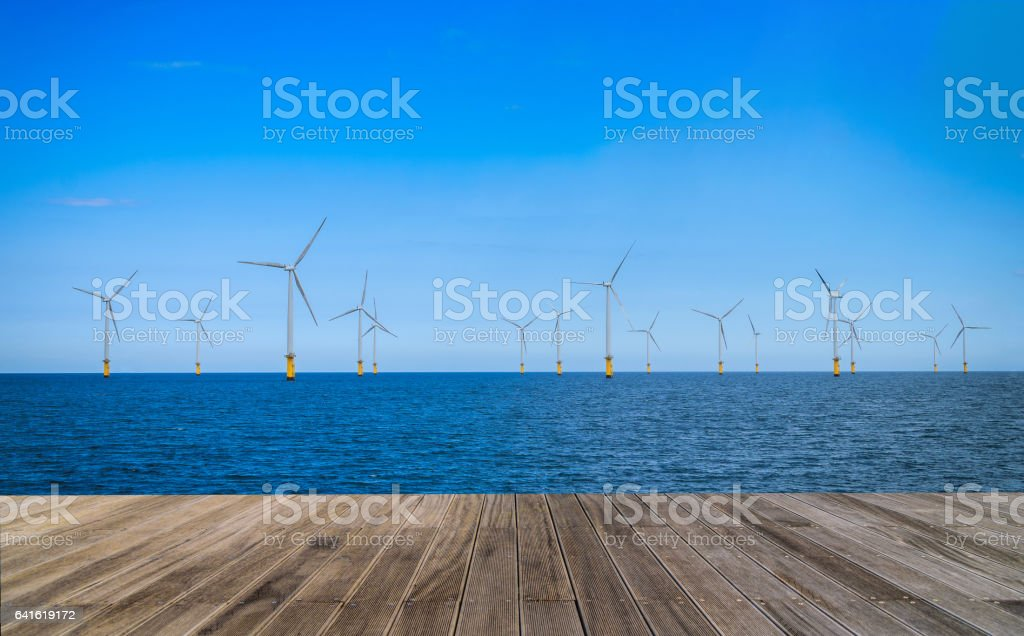 Offshore Wind Turbine in a Wind farm with wooden walkway stock photo
