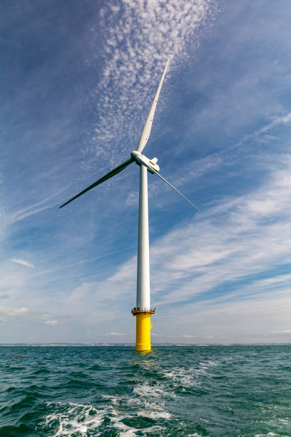 Offshore wind turbine in teal sea with cloud and sunshine stock photo