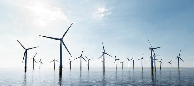 Offshore wind turbines farm on the ocean. Sustainable energy production, clean power.