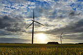 Sunset behind a power generating windturbine on a partly cloudy evening in  Denmark