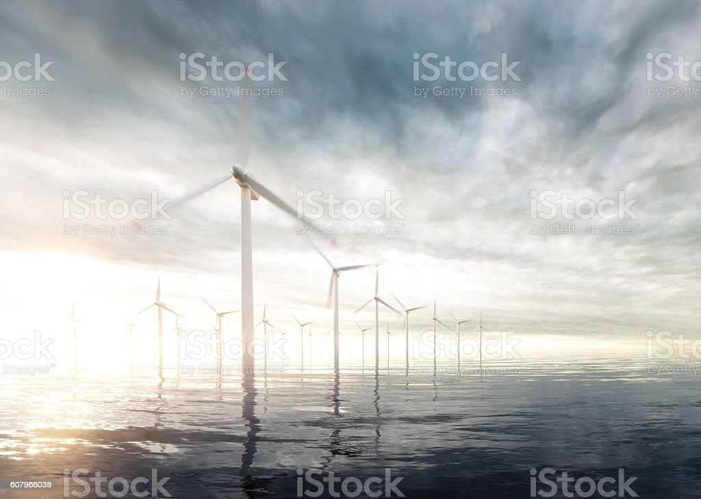 Offshore wind turbines with sunset stormy sky in background stock photo