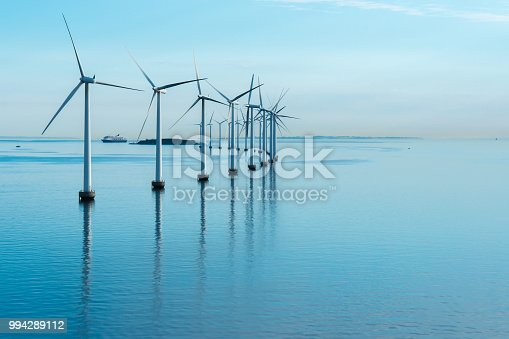 offshore windmill park alternative energy. windmills in the sea with reflection in the morning, denmark