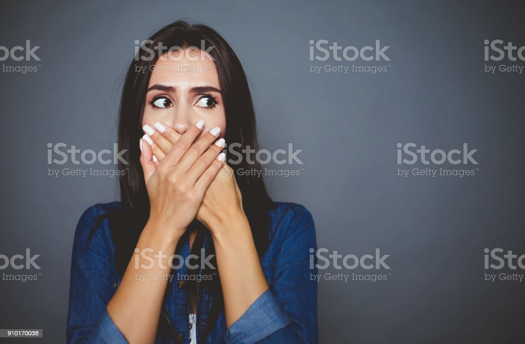 Oh God, how awful. A frightened woman covers her mouth with her hands...
