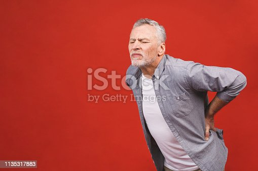 821012164istockphoto Oh, i need a massage! Portrait of a senior aged man having a back pain against a red background. 1135317883