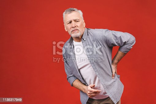 821012164istockphoto Oh, i need a massage! Portrait of a senior aged man having a back pain against a red background. 1135317949