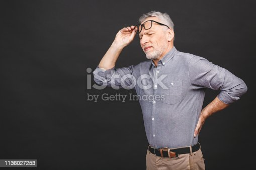 821012164istockphoto Oh, i need a massage! Portrait of a senior aged man having a back pain against a black background. 1136027253
