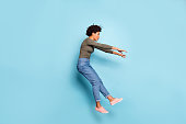 Oh my god. Full length photo of dark skin wavy lady jumping high blown, away by strong stormy wind confused wear casual outfit isolated pastel blue color background