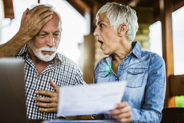 Oh my God, we are way over budget this month! Shocked senior couple reading their home finances in disbelief at balcony. shocked computer stock pictures, royalty-free photos & images