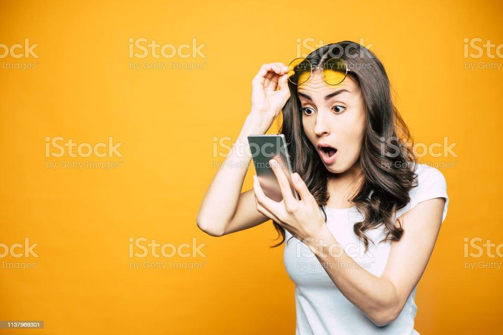 Oh, mijn! Prachtig meisje met een telefoon in haar hand is verrast door iets wat ze zag op het scherm houdt haar bril in de voorkant van fel gele achtergrond. - Royalty-free Alleen volwassenen Stockfoto