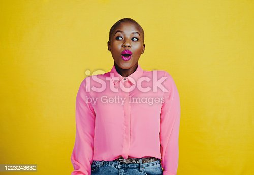 Cropped shot of an attractive young woman looking curious and surprised in studio against a yellow background