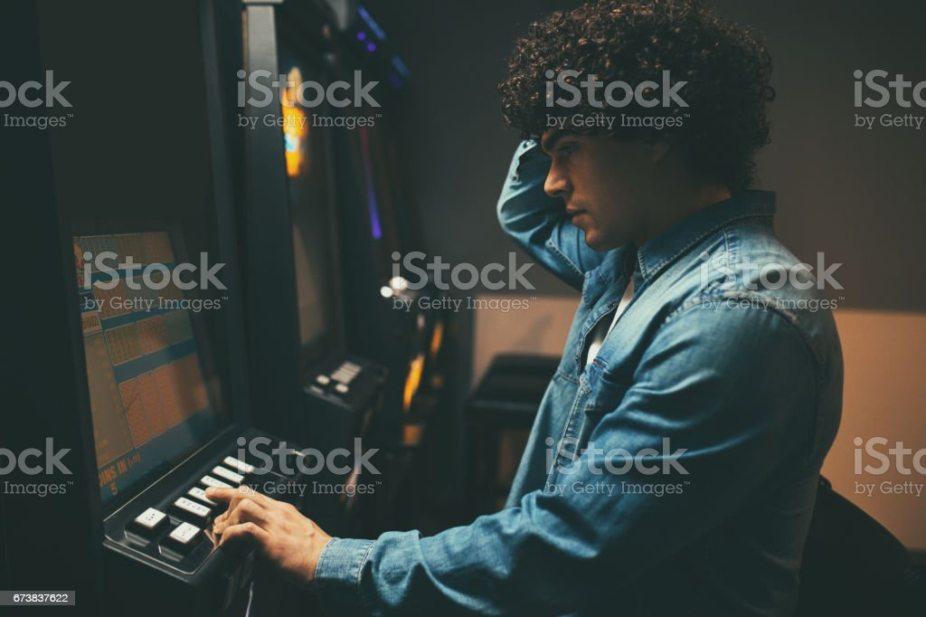 Oh no, I've lost all my money! Worried man loosing his money on a slot machine in a casino. Addict Stock Photo